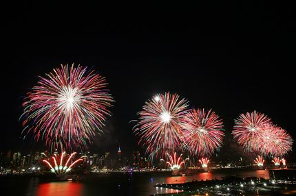 The New York City skyline is seen in the distance as fireworks explode over the Hudson River