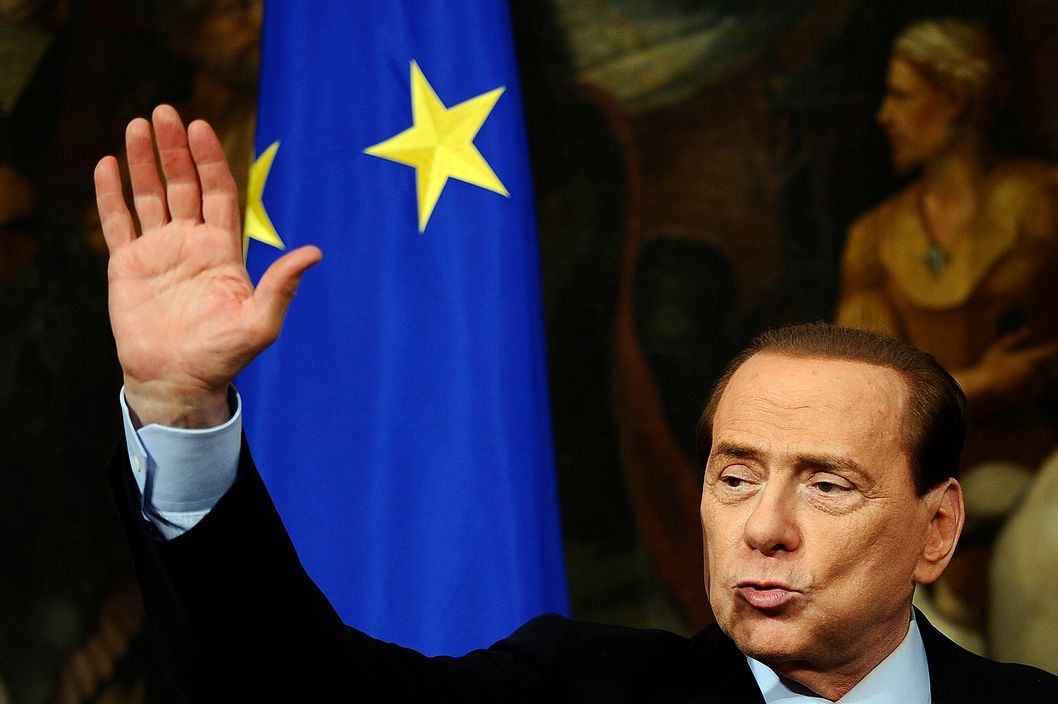 Though this photo was taken in March, Italian Prime Minister Silvio Berlusconi probably didn't know he'd be waving a more permanent good-bye so soon. (FILIPPO MONTEFORTE/AFP/Getty Images)