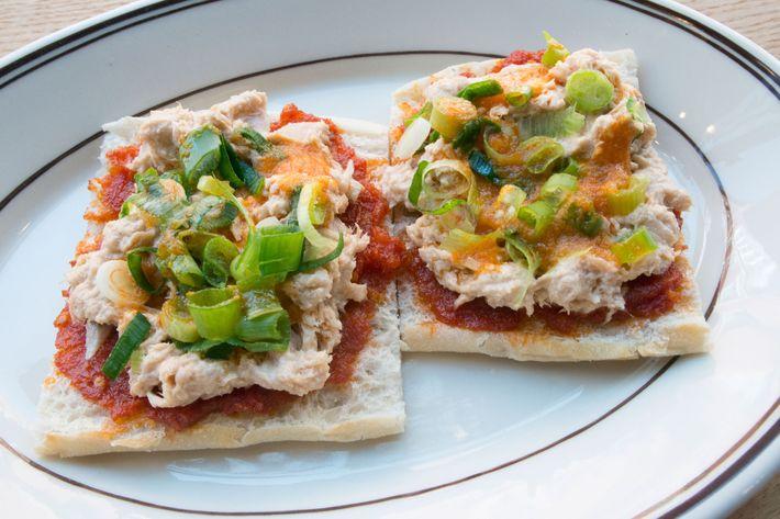 Crostino topped with tuna spread, tomato pesto, scallions, and chile oil.
