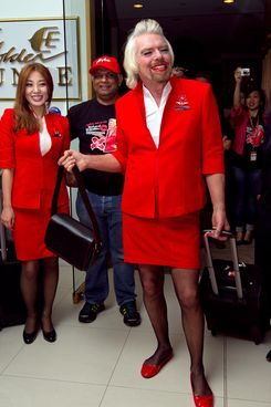 British billionaire Richard Branson (C) smiles next to AirAsia group chief Tony Fernandes (centre L) at Perth Airport on May 12, 2013 before boarding an AirAsia flight to work as a flight attendant bound for Kualu Lumpur. Branson honoured a losing bet with Fernandes over whose Formula One racing team would finish ahead of each other at the Abu Dhabi race during their debut 2010 season.  AFP PHOTO / Tony ASHBY        (Photo credit should read TONY ASHBY/AFP/Getty Images)