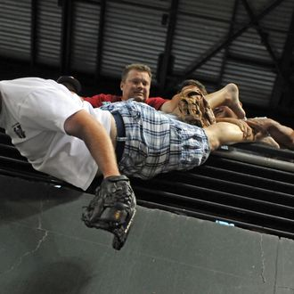 PHOENIX, AZ - JULY 11: Keith Carmickle hangs over the railing above the pool deck after falling over in an attempt to catch a ball during the 2011 State Farm Home Run Derby at Chase Field on July 11, 2011 in Phoenix, Arizona. (Photo by Norm Hall/Getty Images)