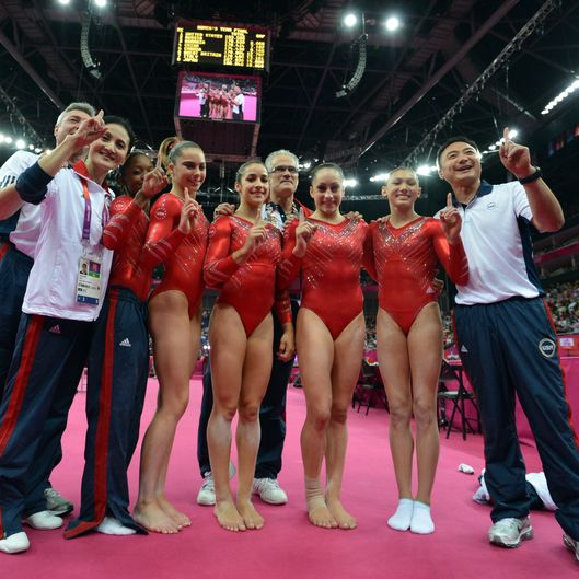 LONDON - JULY 31:  (From 3D-L) US gymnasts Gabrielle Douglas, Mckayla Maroney, Alexandra Raisman, coach John Geddert, Jordyn Wieber and Kyla Ross celebrate winning gold in the women's team of the artistic gymnastics event of the London Olympic Games on July 31, 2012 at the 02 North Greenwich Arena in London. Team US won gold, Team Russia took silver and Team Romania got bronze.  (Photo by BEN STANSALL/AFP/Getty Images) *** Local Caption *** Gabrielle Douglas;Mckayla Maroney;Alexandra Raisman;John Geddert;Jordyn Wieber;Kyla Ross