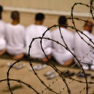 """GUANTANAMO BAY, CUBA - OCTOBER 28: (EDITORS NOTE: Image has been reviewed by U.S. Military prior to transmission)  A group of detainees kneels during an early morning Islamic prayer in their camp at the U.S. military prison for """"enemy combatants"""" on October 28, 2009 in Guantanamo Bay, Cuba. Although U.S. President Barack Obama pledged in his first executive order last January to close the infamous prison within a year's time, the government has been struggling to try the accused terrorists and to transfer them out ahead of the deadline. Military officials at the prison point to improved living standards and state of the art medical treatment available to detainees, but the facility's international reputation remains tied to the """"enhanced interrogation techniques"""" such as waterboarding employed under the Bush administration. (Photo by John Moore/Getty Images)"""