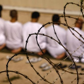 GUANTANAMO BAY, CUBA - OCTOBER 28: (EDITORS NOTE: Image has been reviewed by U.S. Military prior to transmission) A group of detainees kneels during an early morning Islamic prayer in their camp at the U.S. military prison for