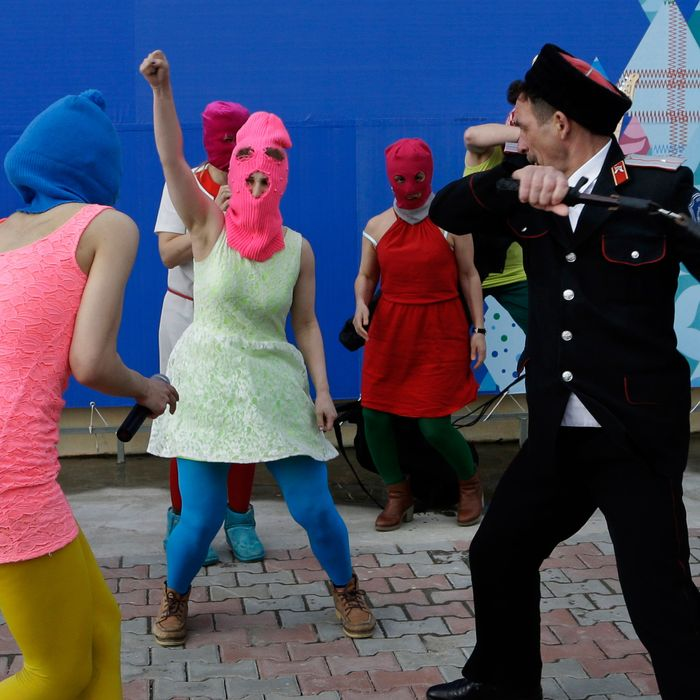 Members of the punk group Pussy Riot, including Nadezhda Tolokonnikova in the blue balaclava and Maria Alekhina in the pink balaclava, are attacked by Cossack militia in Sochi, Russia, on Wednesday, Feb. 19, 2014. The group had gathered in a downtown Sochi restaurant, about 30km (21miles) from where the Winter Olympics are being held. They ran out of the restaurant wearing brightly colored clothes and ski masks and were set upon by about a dozen Cossacks, who are used by police authorities in Russia to patrol the streets. (AP Photo/Morry Gash)