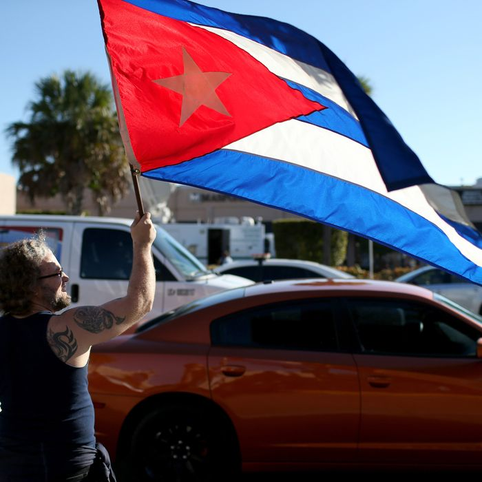 MIAMI, FL - DECEMBER 17: Abdel Rodriguez holds a Cuban flag as he stands outside the Little Havana restaurant Versailles, as people absorb the news that Alan Gross was released from a Cuban prison and that U.S. President Barack Obama wants to change the United States Cuba policy on December 17, 2014 in Miami, United States. Alan Gross, the American contractor had spent five years in Cuban jail. (Photo by Joe Raedle/Getty Images)