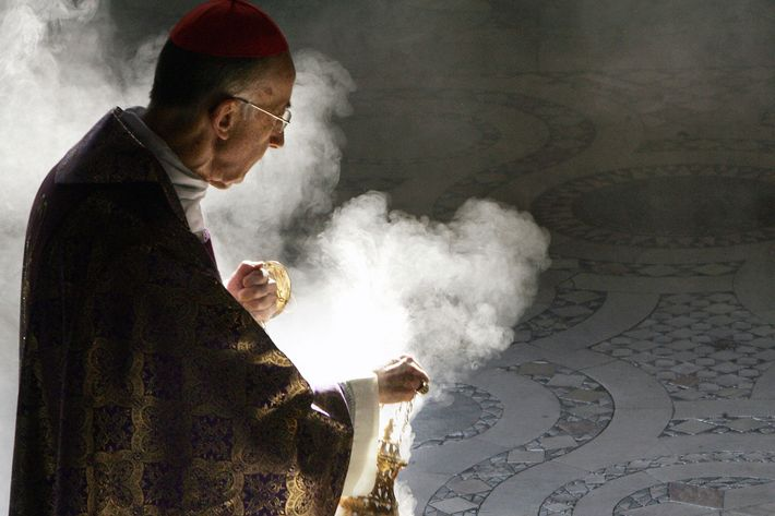 A Catholic cardinal waving incense.