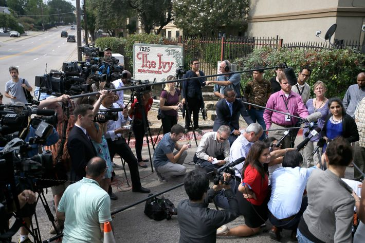 Sally Nuran, far right, in front of microphones, manager of the Ivy Apartments, responds to questions from reporters during a news conference at the main entrance to the complex, Thursday, Oct. 2, 2014, in Dallas.
