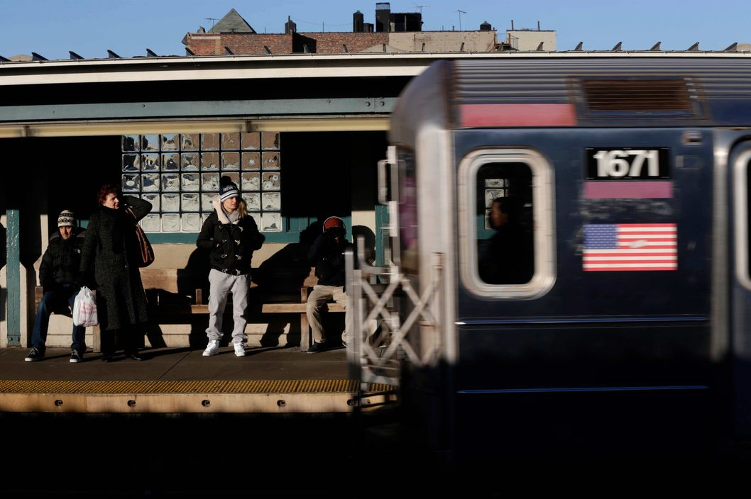 Commuters watch as a train enters the 40th St-Lowry St Station, where a man was killed after being pushed onto the subway tracks, in the Queens section of New York, Friday, Dec. 28, 2012. Police are searching for a woman suspected of pushing the man and released surveillance video Friday of her running away from the station.