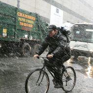 A bicycle courier rides during a brief s