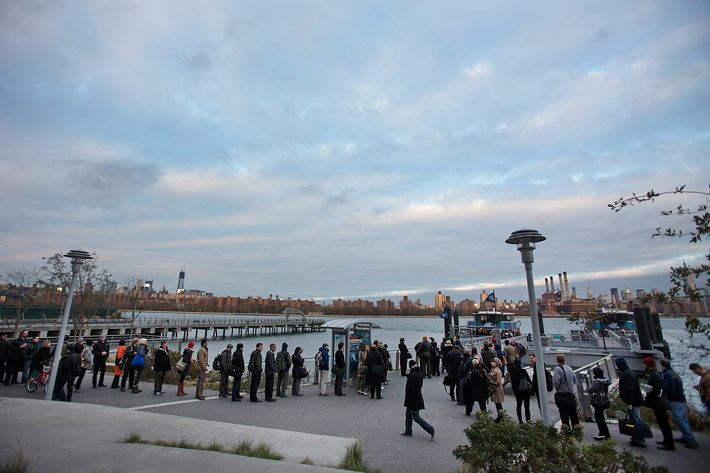 Morning commuters line up to take a Manhattan-bound ferry in the Brooklyn borough of New York, U.S., on Monday, Nov. 5, 2012. Commuters in New York and New Jersey face gasoline lines and miles of traffic jams as the metropolitan area struggles with the chaos that remains in the wake of superstorm Sandy.