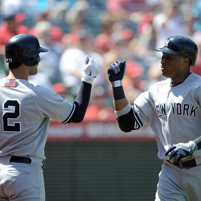 ANAHEIM, CA - SEPTEMBER 11: Robinson Cano #24 of the New York Yankees celebrates his solo homerun with Eric Chavez #12 to trail 3-2 to the Los Angeles Angels of Anaheim during the fourth inning at Angel Stadium of Anaheim on September 11, 2011 in Anaheim, California. (Photo by Harry How/Getty Images)