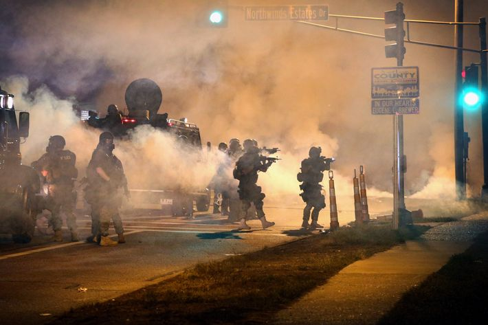 FERGUSON, MO - AUGUST 18:  Police attempt to control demonstrators protesting the killing of teenager Michael Brown on August 18, 2014 in Ferguson, Missouri. Police shot smoke and tear gas to disperse the protestors with as they became unruly.  Brown was shot and killed by a Ferguson police officer on August 9. Despite the Brown family's continued call for peaceful demonstrations, violent protests have erupted nearly every night in Ferguson since his death.  (Photo by Scott Olson/Getty Images)