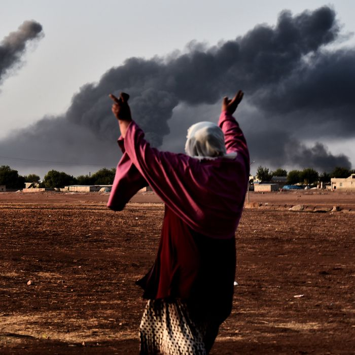 A woman reacts as smoke rises from the the Syrian town of Ain al-Arab, known as Kobane by the Kurds, after a strike from the US-led coalition as it seen from the Turkish - Syrian border in the southeastern village of Mursitpinar, Sanliurfa province, on October 13, 2014.