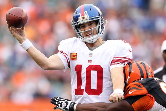 Eli Manning #10 of the New York Giants is hit as he throws the ball by Geno Atkins #97 of the Cincinnati Bengals at Paul Brown Stadium on November 11, 2012 in Cincinnati, Ohio.