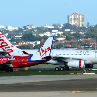 Virgin Australia's Airbus A330-200 (R) taxis past a Virgin Blue Boeing 737-800 (R) after landing at Sydney International Airport on May 4, 2011. Domestic carrier Virgin Blue and its international offshoots, Pacific Blue and V Australia, will all be known as Virgin Australia, with negotiations underway to bring Polynesia Blue under the same umbrella.