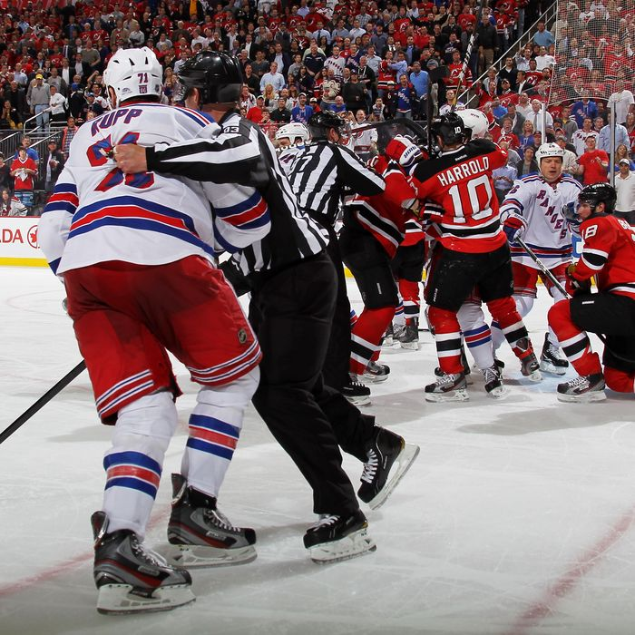Linesman Brian Murphy #93 pulls Mike Rupp #71 of the New York Rangers away from Martin Brodeur #30 after an altercation in the third period of Game Four of the Eastern Conference Final during the 2012 NHL Stanley Cup Playoffs at the Prudential Center on May 21, 2012 in Newark, New Jersey.