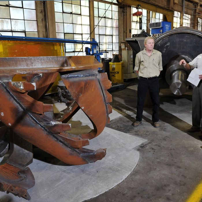 US President Barack Obama(R) looks at dredging equipment which will be heading to Bangladesh during a tour of Ellicott Dredges with Ellicott Dredges President Peter Bowe on May 17, 2013 in Baltimore, Maryland. Obama is visiting Baltimore on what the administration called