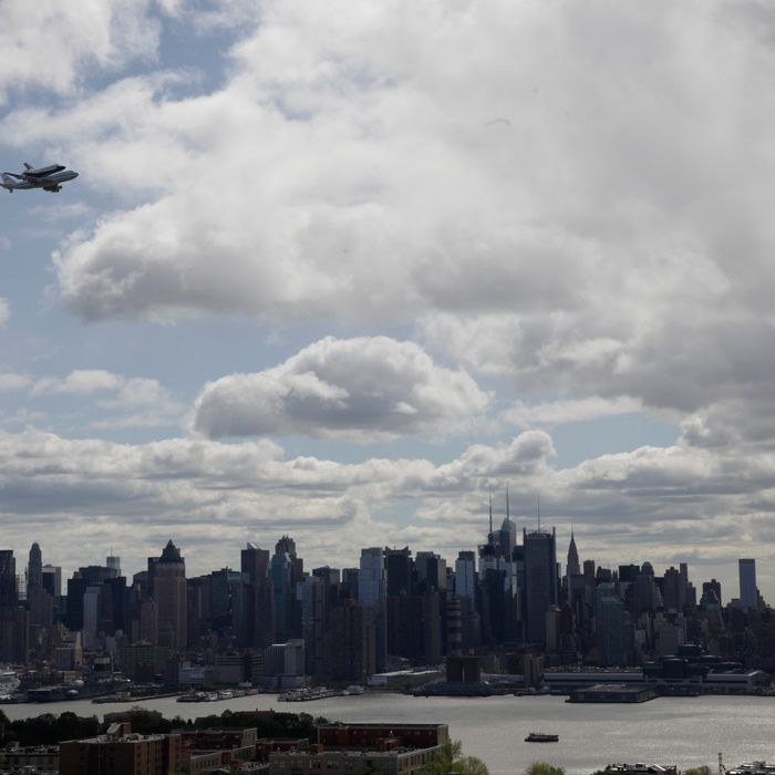 Space shuttle Enterprise, riding on the back of the NASA 747 Shuttle Carrier Aircraft, cruises over the New York City skyline.
