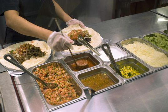 Workers prepare burritos at a Chipotle Mexican Grill in Midtown in New York.