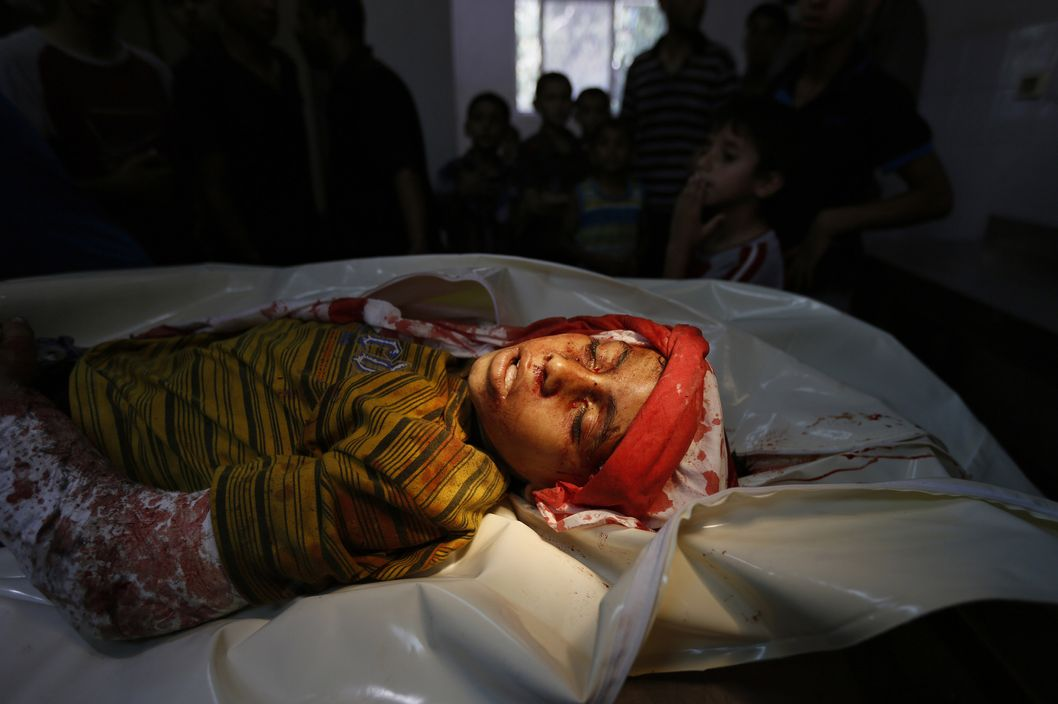The body of a ten-year old Palestinian boy, who was killed in an Israeli air strike on the Sheikh Radwan neighbourhood in northern Gaza City, lies at the city's Al-Shifa hospital, on August 8, 2014. Israeli warplanes struck targets across Gaza in retaliation to rocket fire after a 72-hour truce expired without a breakthrough on a longer-term ceasefire.