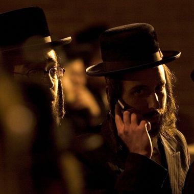 Members of the Satmar Hassidic Jewish community wait outside the Satmar Synagogue on Rodney street on April 24, Brooklyn, New York City.