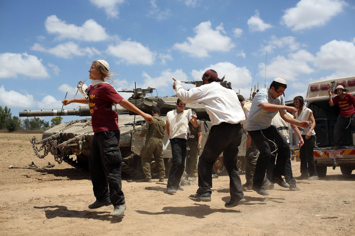 """Young Orthodox Jews dance to support the soldiers at an army deployment area near Israel's border with the Gaza Strip, on July 17, 2014. An Israeli official said the Jewish state had agreed a ceasefire with Hamas that will begin at 0300 GMT Friday, but the Islamist movement said it had """"no information"""" on a deal. AFP PHOTO /MENAHEM KAHANA        (Photo credit should read MENAHEM KAHANA/AFP/Getty Images)"""