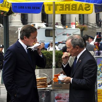 New York City Mayor Michael Bloomberg and British Prime Minister David Cameron (L) share a hot dog outside of Penn Station on July 21, 2010. Cameron arrived in the city by train for meetings.