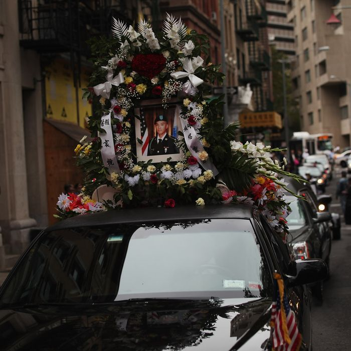 NEW YORK, NY - OCTOBER 13: A portrait of U.S. Army Pvt. Danny Chen is viewed on a car in his funeral procession in Chinatown on October 13, 2011 in New York City. Pvt. Chen who had been in Afghanistan for two months, was found dead with a gunshot wound below his chin on Oct. 3. While preliminary signs suggest Pvt. Chen killed himself, the Army has told the soldiers parents that he was subjected to taunting and violence by some of the soldiers with whom he served with. (Photo by Spencer Platt/Getty Images)