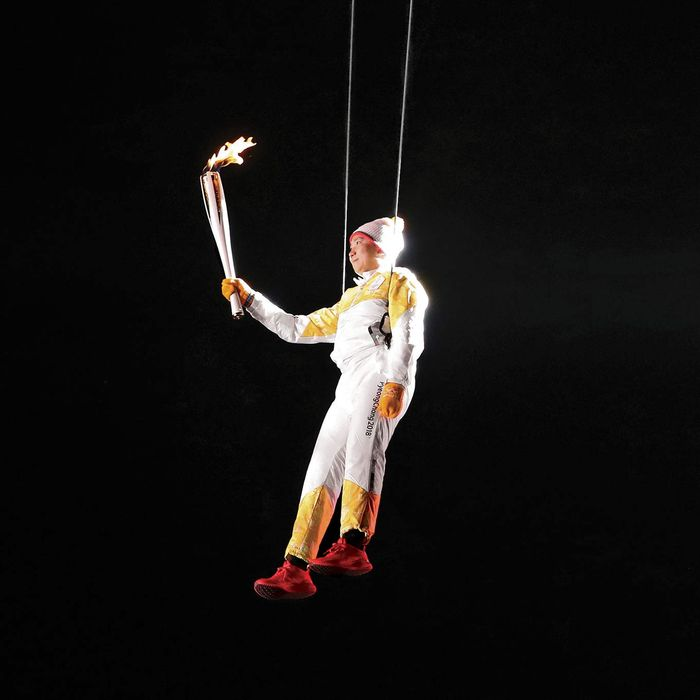 South Korean athlete Ryu Seung-min carries the Olympic torch as he hangs from a wire during the Olympic Torch Relay.