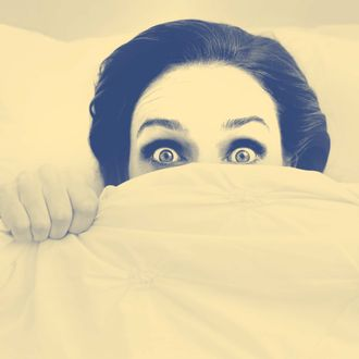 A young woman peeking out from under her ned sheet with a frightened expression.