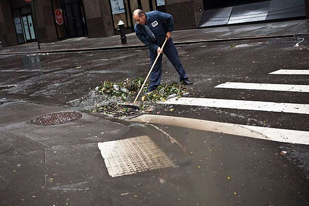 NEW YORK, NY - OCTOBER 30:  Ramiro Arcos sweeps debris from a storm drain while cleaning up damage caused by Hurricane Sandy on October 30, 2012 in the Financial District of New York, United States. The storm has claimed at least 16 lives in the United States, and has caused massive flooding across much of the Atlantic seaboard. US President Barack Obama has declared the situation a 'major disaster' for large areas of the US East Coast including New York City.   (Photo by Andrew Burton/Getty Images)