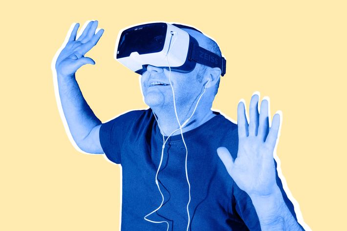 Man wearing ZEISS VR ONE virtual reality VR plastic goggles with bracket for Samsung Galaxy S5 Android smartphone and in-ear headphones, hands up