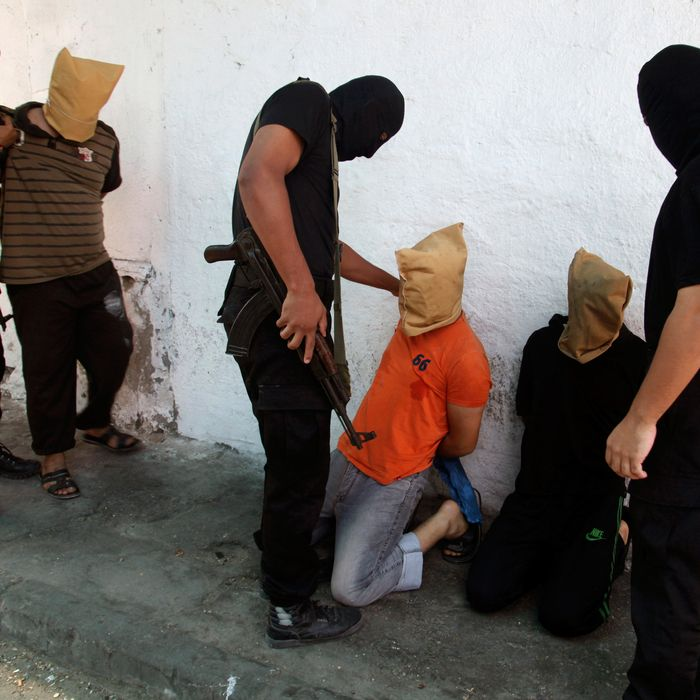 Hamas militants grab Palestinians suspected of collaborating with Israel, before executing them in Gaza City August 22, 2014.