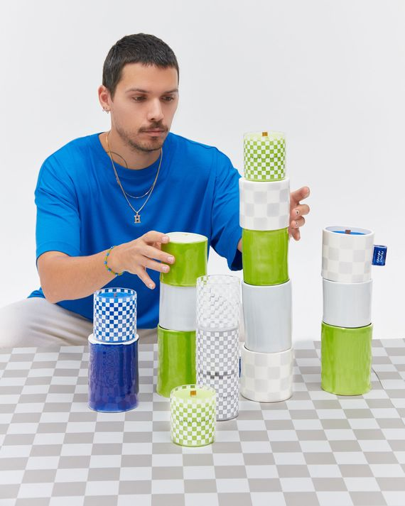 Portrait of a man wearing a blue t-shirt sitting at a checkerboard table stacking assorted candles in ceramic and glass vessels