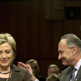US Secretary of State designate Senator Hillary Clinton (L) is patted on the back by US Senator Charles Schumer (R), D-NY, during her confirmation hearing on Capitol Hill in Washington, DC, January 13, 2009. AFP PHOTO/Jim WATSON (Photo credit should read JIM WATSON/AFP/Getty Images)