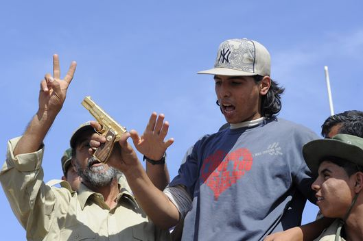 Libyan National Transitional Council (NTC) fighters hold what they claim to be the gold-plated gun of ousted Libyan leader  Moamer Kadhafi at the site where the latter was allegedly captured in the coastal Libyan city of Sirte on October 20, 2011.  A Libyan National Transitional Council (NTC) commander had told AFP that Kadhafi was captured as his hometown Sirte was falling, adding that the ousted strongman was badly wounded.  AFP PHOTO/PHILIPPE DESMAZES (Photo credit should read PHILIPPE DESMAZES/AFP/Getty Images)
