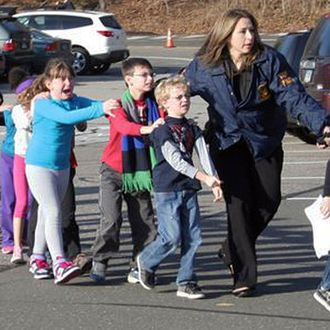 In this photo provided by the Newtown Bee, Connecticut State Police lead children from the Sandy Hook Elementary School in Newtown, Conn., following a reported shooting there Friday, Dec. 14, 2012. (AP Photo/Newtown Bee, Shannon Hicks) MANDATORY CREDIT