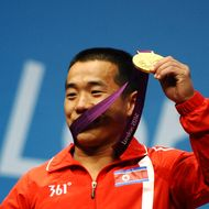 Yun Chol Om of DPR Korea celebrates with the gold medal on the podium after the Men's 56kg Weightlifting on Day 2 of the London 2012 Olympic Games at ExCeL on July 29, 2012 in London, England.