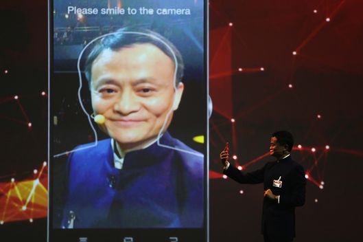Alibaba Group Executive Chairman Jack Ma presents a new facial recognition feature of the Alibaba portal as he speaks at the opening ceremony of the 2015 CeBIT technology trade fair on March 15, 2015 in Hanover, Germany. China is this year's CeBIT partner. CeBIT is the world's largest tech fair and will be open from March 16 through March 20.  (Photo by Sean Gallup/Getty Images)