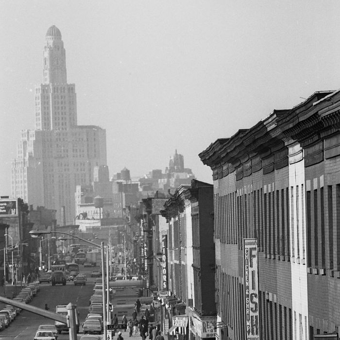 View of the street with people milling about and traffic at the intersection of Claver Place and Fulton Avenue in the Bedford Stuyvesant section of Brooklyn, 1968. The Williamsburgh Savings Bank tower can be seen in the distance.