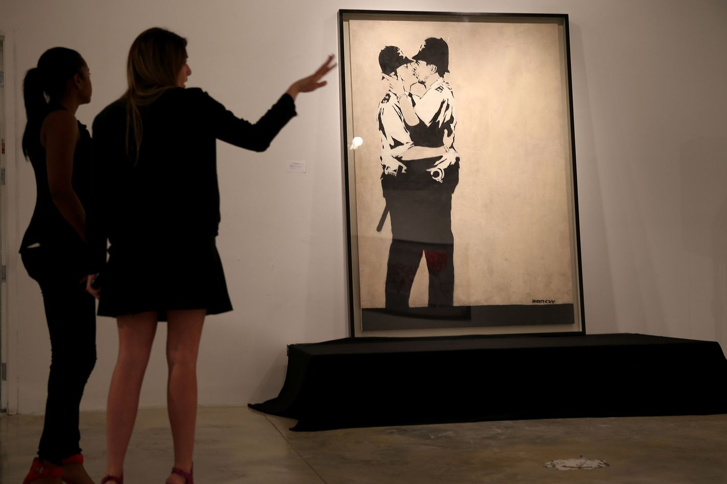 """People stand near a piece of art titled """"Kissing Coppers"""" by the artist Banksy before it went to auction at the Fine Art Auctions Miami Street Art Auction at LMNT on February 18, 2014 in Miami, Florida. Three pieces of art by Banksy along with about 50 other lots by other artists such as  Kenny Scharf, Basquiat, Bambi, Speedy Graphito went on the auction block."""