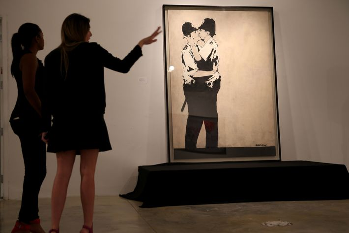 "People stand near a piece of art titled ""Kissing Coppers"" by the artist Banksy before it went to auction at the Fine Art Auctions Miami Street Art Auction at LMNT on February 18, 2014 in Miami, Florida. Three pieces of art by Banksy along with about 50 other lots by other artists such as  Kenny Scharf, Basquiat, Bambi, Speedy Graphito went on the auction block."