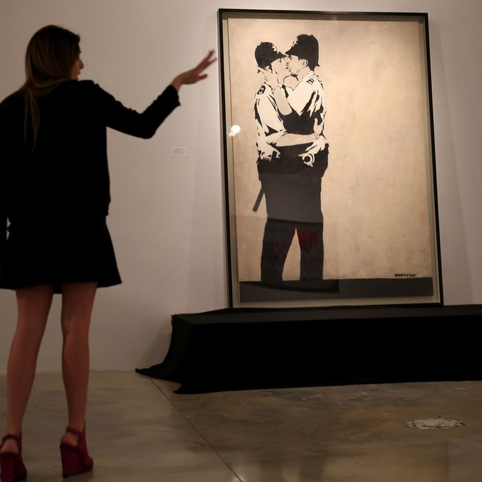 People stand near a piece of art titled