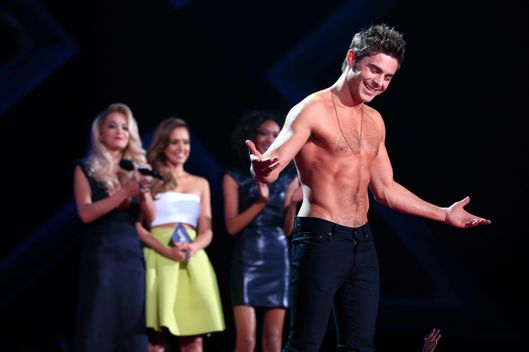 LOS ANGELES, CA - APRIL 13:  Recording artist Rita Ora (L) and actress Jessica Alba (C) watch as actor Zac Efron accepts the Best Shirtless Performance award for 'That Awkward Moment' onstage at the 2014 MTV Movie Awards at Nokia Theatre L.A. Live on April 13, 2014 in Los Angeles, California.  (Photo by Christopher Polk/Getty Images for MTV)