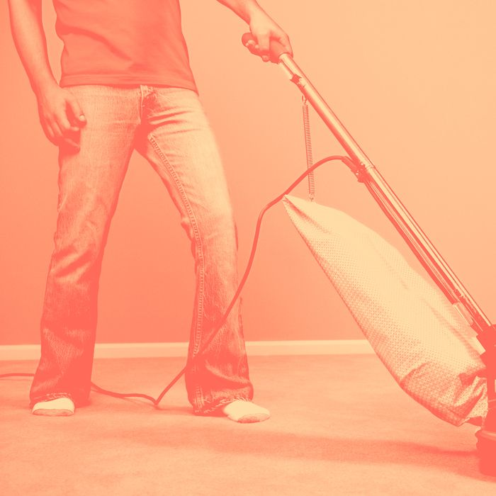 Low section of young man vacuuming