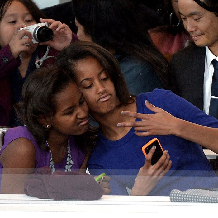 Sasha (L) and Malia Obama, daughters of US President Barack Obama, take a photo of themselves during the Presidential Inaugural Parade on January 21, 2013 in Washington, DC.
