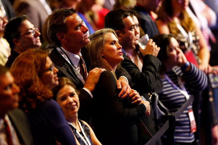 People standing in the crowd react while watching election results displayed on a television during Mitt Romney's campaign election night event at the Boston Convention & Exhibition Center on November 6, 2012 in Boston, Massachusetts. Voters went to polls in the heavily contested presidential race between incumbent U.S. President Barack Obama and Republican challenger Mitt Romney.