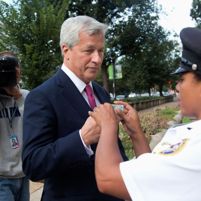 JPMorgan Chase Chairman, President and CEO Jamie Dimon presents his driver's license to Justice Department security officer G. Rocher, as he arrives at the Justice Department in Washington, Thursday, Sept. 26, 2013. An $11 billion national settlement is under discussion to resolve claims over JPMorgan's handling of mortgage-backed securities in the run-up to the recession, said a government official familiar with ongoing negotiations among bank, federal and New York state officials.