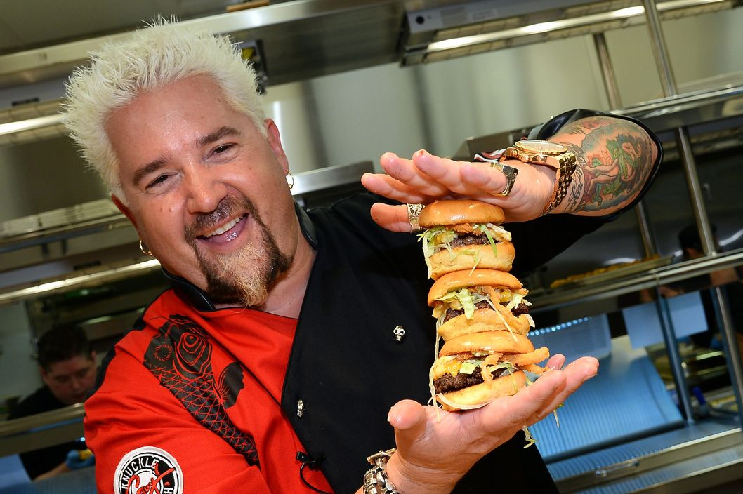 Chef and television personality Guy Fieri holds hamburgers in the kitchen during a welcome event for Guy Fieri's Vegas Kitchen & Bar at The Quad Resort & Casino on April 4, 2014 in Las Vegas, Nevada. The restaurant opens on April 17.